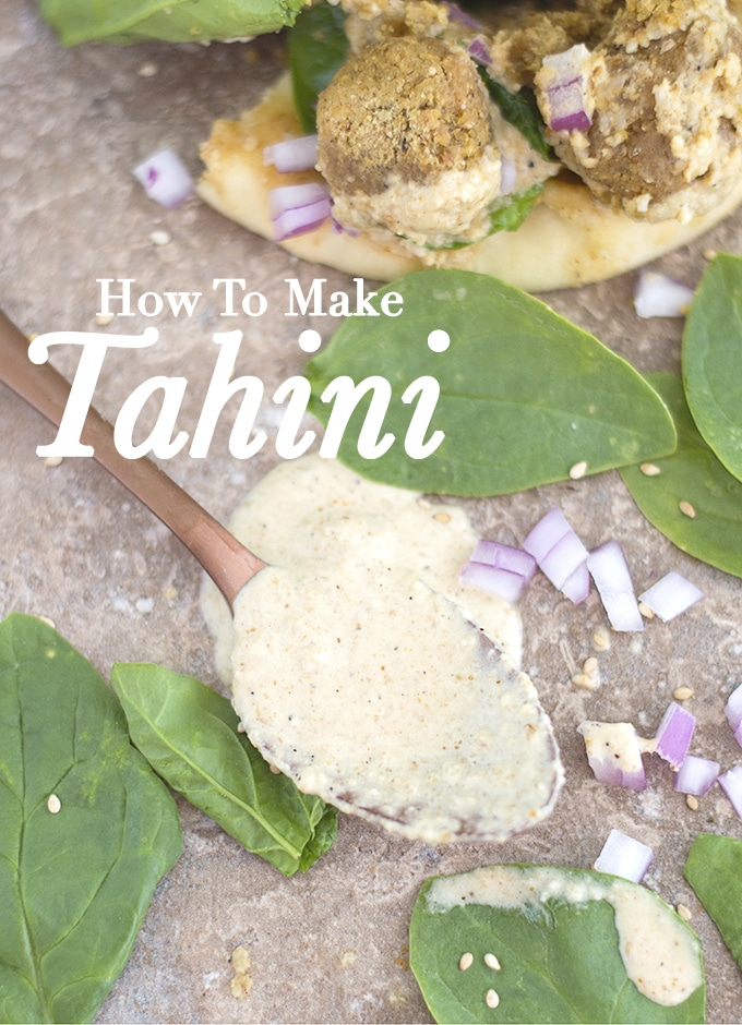 Overhead View of a Bronze Spoon Dipped in the Tahini Sauce Laying Flat on a Brown Tile. Some of the Tahini is Spilled Around the Spoon. Baby Spinach, Falafal Balls, Sesame Seeds and Finely Chopped Red Onions are Strewn Around in the Photo. In the Left Background, A Partial View of a Falafel Sandwich is Visible. How to Make Tahini?