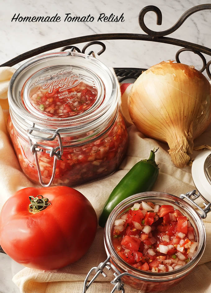 2 jars of tomato relish in a metal round tray with tomato, jalapeno and onions