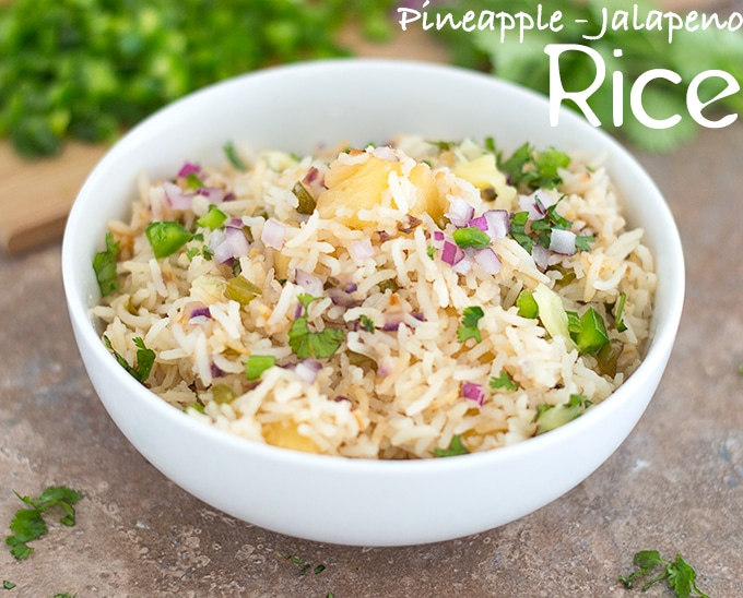 45 Degree View of a White Bowl Filled with Cooked Rice, Pineapple, Jalapeno, Red Onions and Cilantro. In the Background, Chopped Jalapeno, Red Onions and Cilantro leaves are Visible - Pineapple fried Rice