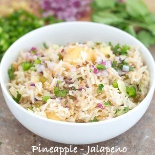 Front View of a White Bowl Filled with Cooked Rice, Pineapple, Jalapeno, Red Onions and Cilantro. In the Background, Chopped Jalapeno, Red Onions and Cilantro leaves are Visible - Pineapple fried Rice