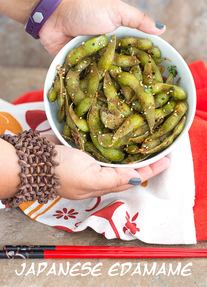 The Author Holding a Medium White Bowl Filled with The Spiced Edamame Pods. In the Background, there is a White and Orange Cloth and a Pair of Chopsticks in Front - Spicy Edamame Recipe