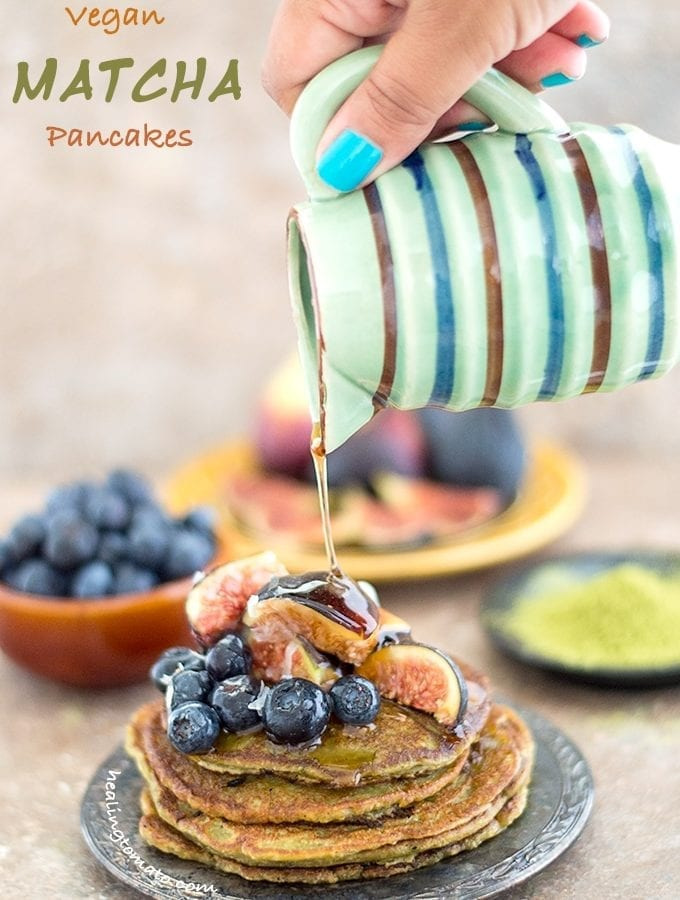 Front View of a Plate of Vegan Pancakes Topped with Figs and Blueberry. The Author's Hand is Holding a Small Ceramic Jar Which is Drizzling Maple Syrup on the Stack. In the Background, a Bowl with Blueberries, a Plate with Figs and a Black Saucer Filled with Matcha Powder is Visible