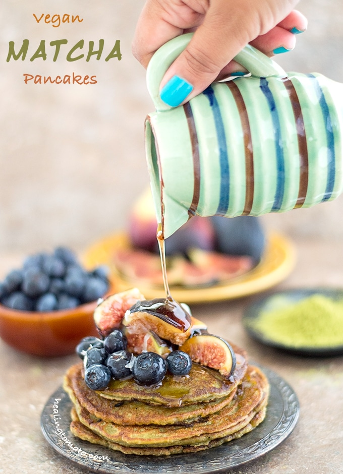 Front View of a Plate of Vegan Pancake Recipe Topped with Figs and Blueberry. The Author's Hand is Holding a Small Ceramic Jar Which is Drizzling Maple Syrup on the Stack. In the Background, a Bowl with Blueberries, a Plate with Figs and a Black Saucer Filled with Matcha Powder is Visible
