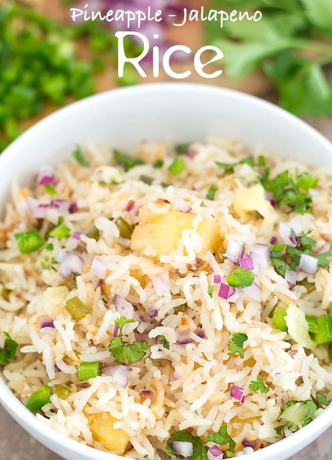 Overhead View of a White Bowl Filled with Cooked Rice, Pineapple, Jalapeno, Red Onions and Cilantro. In the Background, Chopped Jalapeno, Red Onions and Cilantro leaves are Visible - Pineapple fried Rice