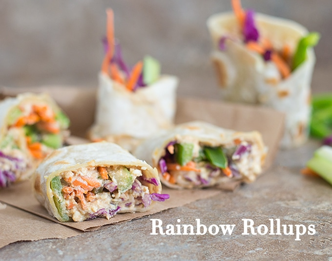 Closeup View of Rainbow Rollups With Red Cabbage, Carrots, Bell Peppers and Celery. Wrapped in Tortillas and Placed on Brown Paper. 2 Back-To-School Recipes