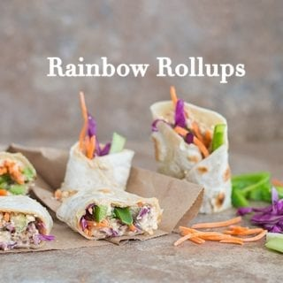 Rainbow Rollups With Red Cabbage, Carrots, Bell Peppers and Celery. Wrapped in Tortillas and Placed on Brown Paper. Shredded Veggies are Placed on the Right. 2 Back-To-School Recipes