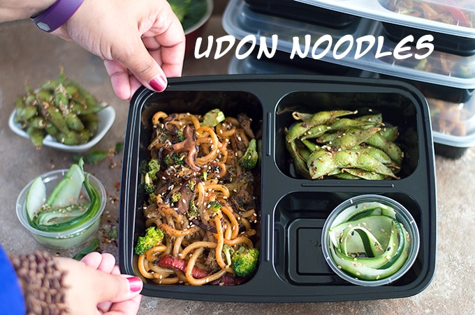 Author's Hands Holding One Meal Prep Container in Tilted Position to Show Contents. Containers Filled with Stir Fried Noodles in the Main Compartment. Other 2 Contain Edamame Pods and Cucumber Salad
