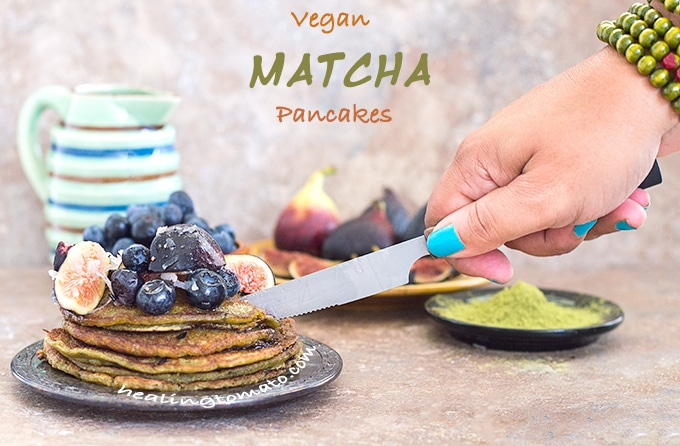 Front View of a Plate of Vegan Pancake Recipe Topped with Figs and Blueberry. The Author's Hand Is Cutting into the Stack with a Butter Knife. In the Background, a Bowl with Blueberries, a Plate with Figs and a Black Saucer Filled with Matcha Powder is Visible