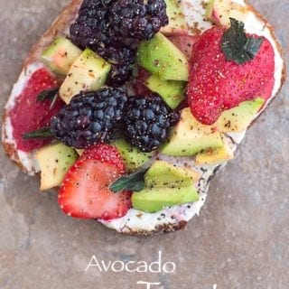Overhead View of A Toasted Slice of Bread with Vegan Cream Cheese Spread and Topped with Avocado, Fresh Strawberries and Blackberries