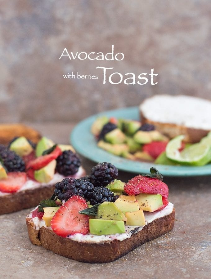 Front View of A Toasted Slice of Bread with Vegan Cream Cheese Spread and Topped with Avocado, Fresh Strawberries and Blackberries. A Similar Toast is in the Background on the Left and a Green Plate with the Fruit Mixture is in the Right Background