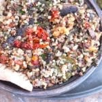 Closeup View of a Rustic Bowl Filled with Cooked Quinoa, Mushrooms, Sundried Tomatoes, Kale and Walnuts