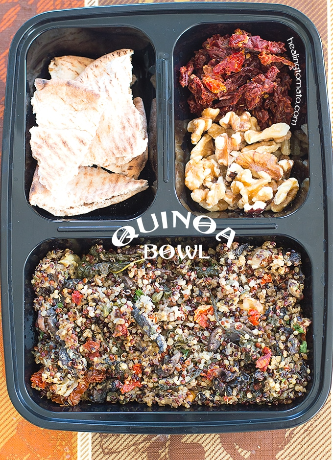 A Meal Prep Container with 3 Compartments. The Main Compartment is filled with Cooked Quinoa. One Compartment has Cut Pieces of Pita Bread. The Other has Sundried Tomatoes and Walnuts. Quinoa Bowl
