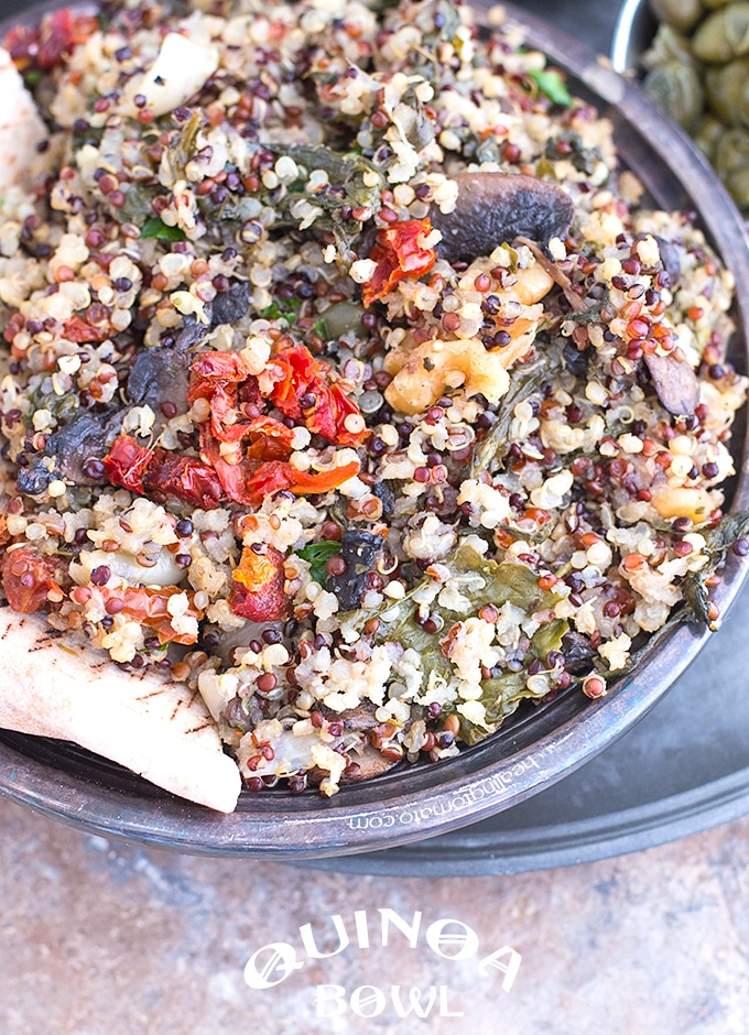 Closeup View of a Rustic Quinoa Bowl Filled with Cooked Quinoa, Mushrooms, Sundried Tomatoes, Kale and Walnuts
