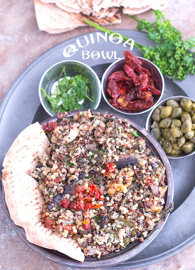 Overhead view of Grey Plate Loaded with 4 Bowls. Main Bowl is Filled with Cooked Quinoa and a 1/2 of a Pita Bread on the Side. 3 Smaller Steel Bowls have Parsley, Sundried Tomatoes and Capers