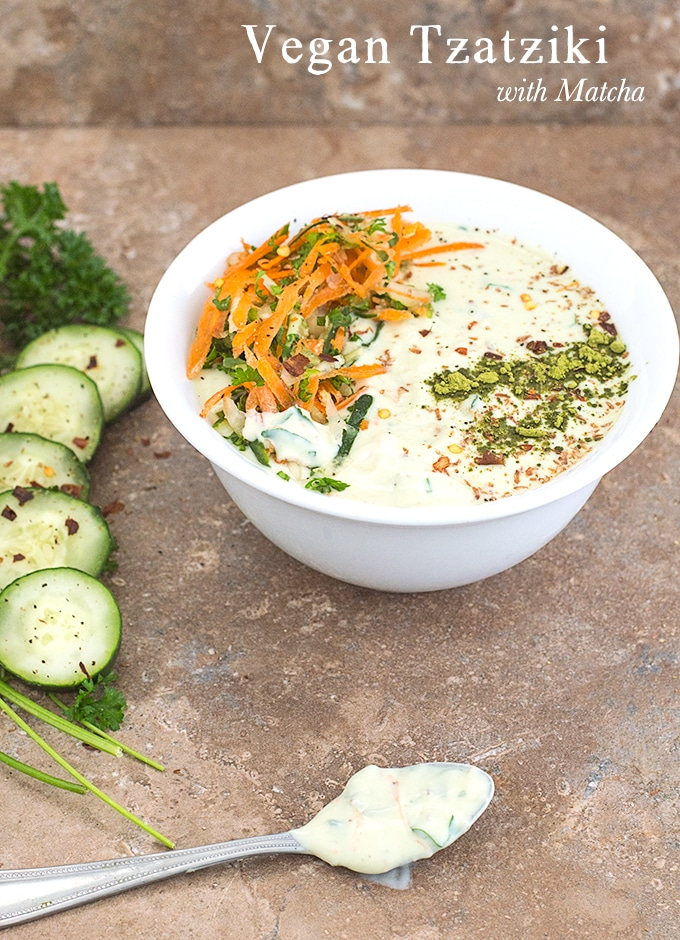 Front view of a white bowl filled with Vegan Tzatziki with carrot saalad on the left and matcha powder line on the right. To the left of the bowl, Parsley, cucumber and lime rounds are placed in an arc