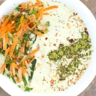 Closeup view of a white bowl filled with Tzatziki. It has carrot saalad on the left arranged in an arc and matcha powder line on the right.
