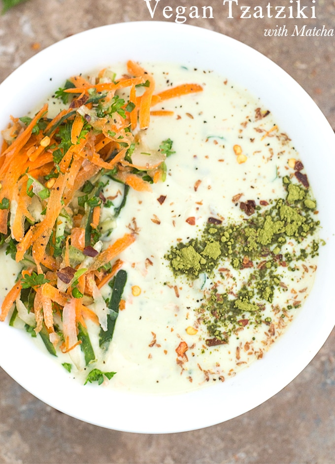 Closeup view of a white bowl filled with Vegan Tzatziki. It has carrot saalad on the left arranged in an arc and matcha powder line on the right.