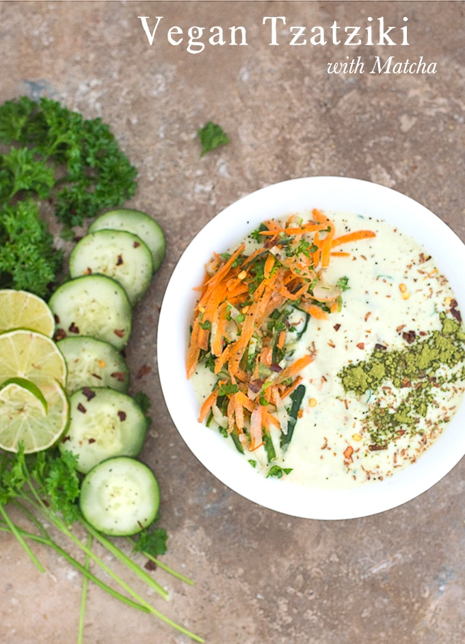 Overhead view of a white bowl filled with Vegan Tzatziki. It has carrot saalad on the left arranged in an arc and matcha powder line on the right. To the left of the bowl, Parsley, cucumber and lime rounds are placed in an arc