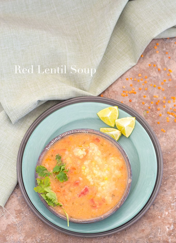 Overhead View of a Bowl With Red Lentil Soup on A Green Plate. 3 Wedges of Lime on The Top of the Plate. A Green Cloth on the Left and Uncooked Red Lentils Around the Plate.