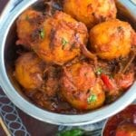 Overhead view of a steel bowl filled with potatoes cooked in Indian Spices. In the Background, curry, naan and papad are visible - Bombay Potatoes recipe