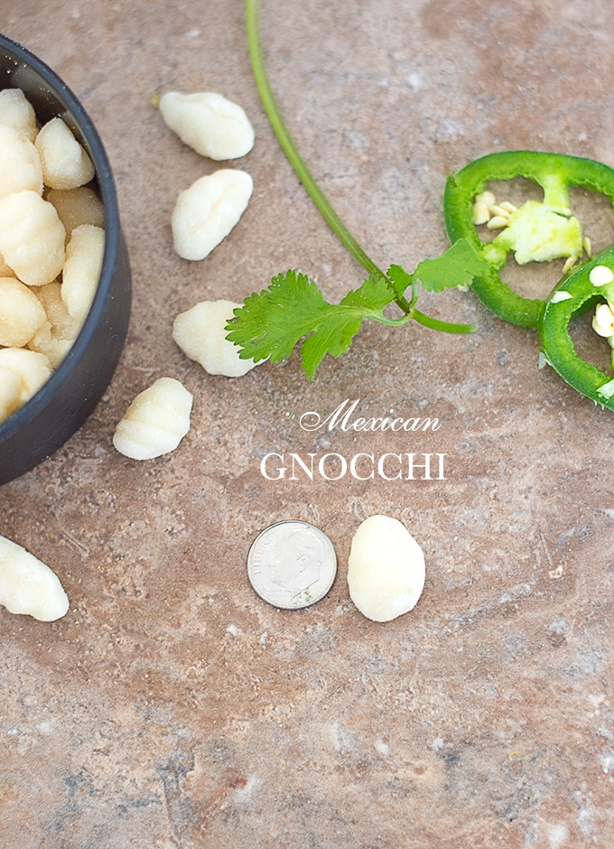 Overhead View of a mini gnocchi next to a dime. Photo also includes jalapeno, cilantro and a measuring cup with mini gnocchi - vegan Mexican Gnocchi