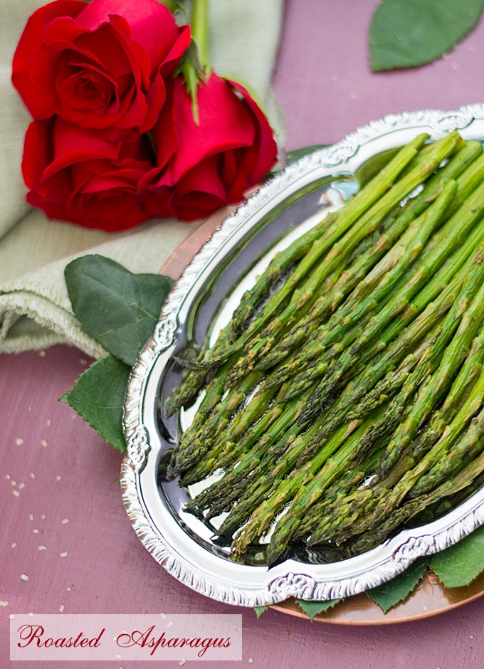 Overhead view of roasted asparagus on a silver plate with red roses on a green cloth sitting next to it - Roasted Vegetables