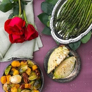 Overhead view of 3 plates arranged in an arc. Plates have Roasted Butternut squash, Cabbage Wedges and Roasted asparagus respectively. Top left of the picture has a green cloth with red roses