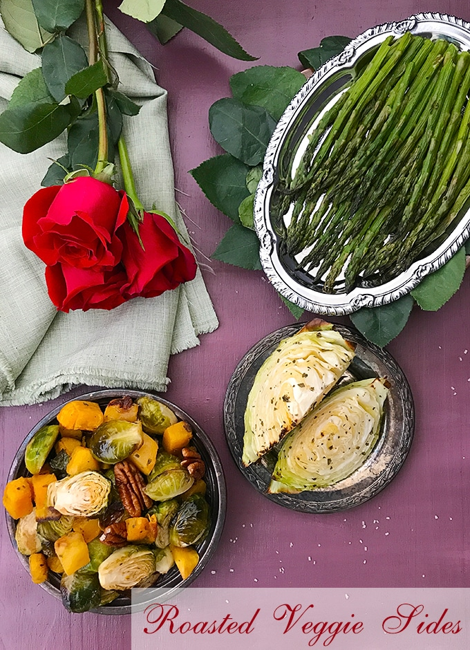 Overhead view of 3 plates arranged in an arc. Plates have Roasted Butternut squash, Cabbage Wedges and Roasted asparagus respectively. Top left of the picture has a green cloth with red roses - Roasted Vegetables
