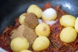 Spices and salt added to the pan - Vegan Bombay Potatoes