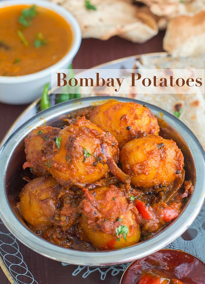 Overhead view of a steel bowl filled with potatoes cooked in Indian Spices. In the Background, curry, naan and papad are visible - Bombay Potatoes