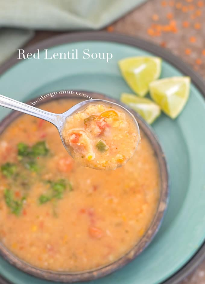 Overhead View of a Spoon Filled with Red Lentil Soup Over a Bowl Filled with Red Lentil Soup