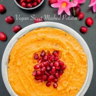 Overrhead view of a steel bowl with vegan mashed sweet potato with pomegranate in the middle