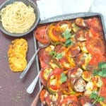 Overhead view of a Sheet Pan Filled With Ratatouille and 3 Spoons Coming Out at an Angle. A Grey Plate with Cooked Spaghetti is Visible on the Top