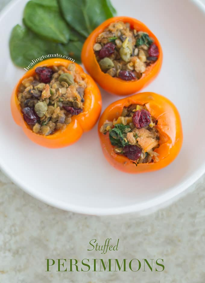 Three Stuffed Persimmons on a white plate with spinach leaves