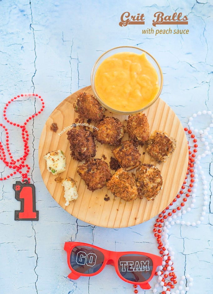 Overhead View of Grit Balls on a Brown Board with a Peach Sauce in a Small Bowl on the Side