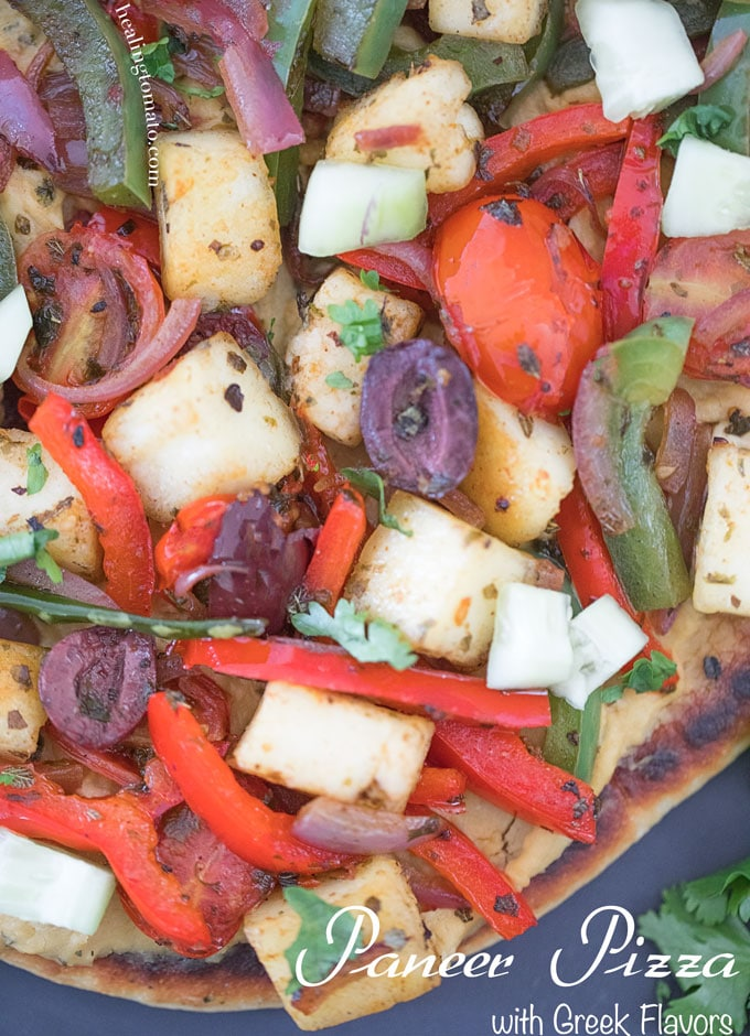 Closeup view of Paneer Pizza with raosted bell peppers, tomatoes, naan, olives and hummus on naan bread
