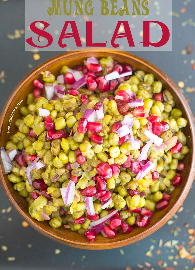 Overhead view of a wooden brown bowl filled with mung beans, pomegranate and onions