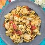 Closeup view of a grey plate filled with Vegan Orecchiette Pasta, roasted tomatoes and pearl onions
