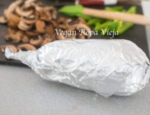 Eggplant wrapped in aluminium foil. Chopped veggies in the background