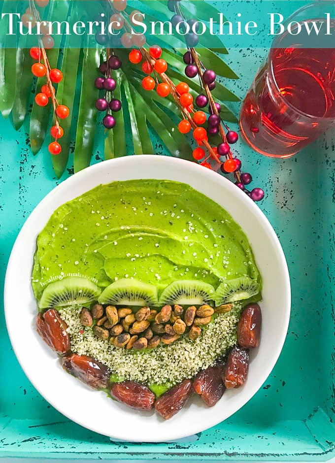 Overhead View of a Turmeric Smoothie Bowl with Green Smoothie on one half. The other half has Kiwi, Pistachios, Dates and Hemp Seeds