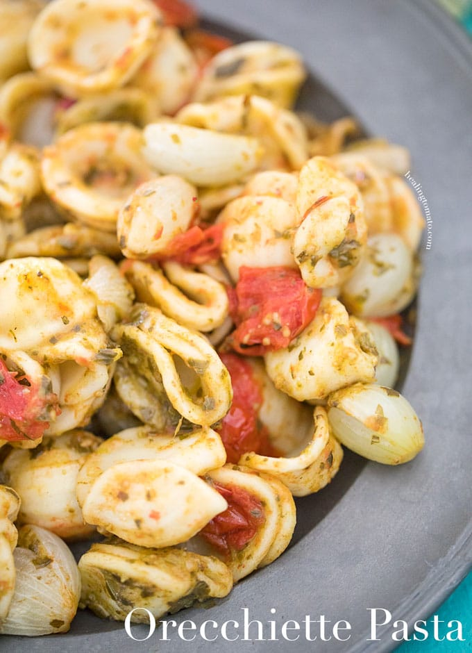 Closeup view of a grey plate filled with Vegan Orecchiette Pasta, roasted tomatoes and pearl onions - cold pasta