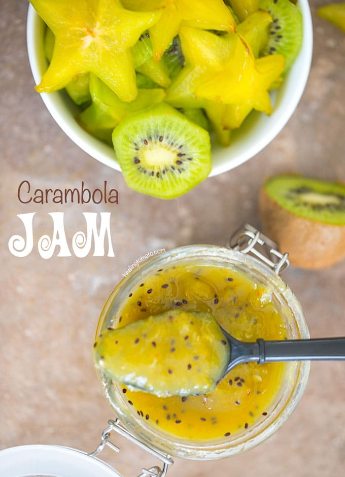 Overhead View of A Jar With Star Fruit Carambola Jam With a Black Spoon Laying on the Surface. Background has a bowl of chopped carambola and kiwi