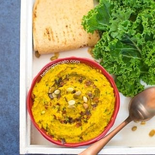 Overhead View of a White Tray with a red bowl in it. Bowl contains Spicy Kale Hummus and is surrounded by Kale leaves, spoon and pita bread