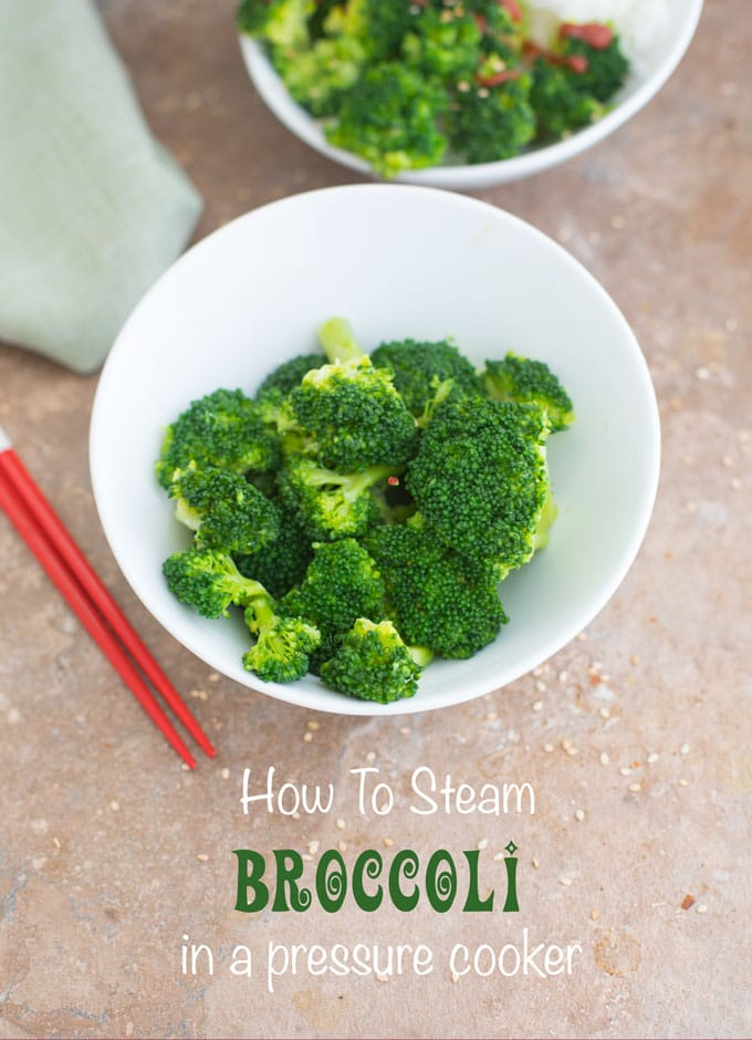 Closeup view of a white bowl of steamed broccoli with red chopsticks next to it - Pressure Cooker Steamed Broccoli