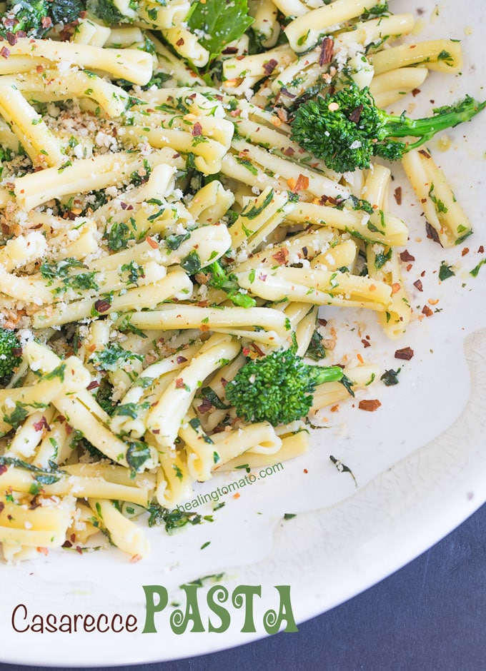 Closeup view of a white bowl filled with casarecce pasta, roasted broccolini, vegan butter sauce and panko bread crumbs as garnish - Cold Pasta recipe