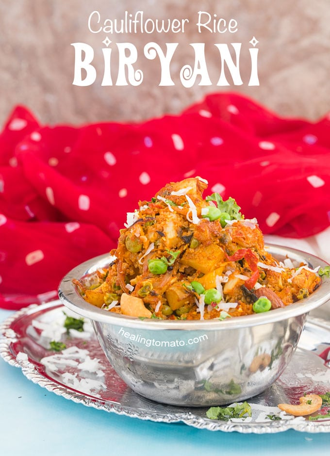 Front view of a steel bowl filled with cauliflower rice biryani with Indian scarves next to it