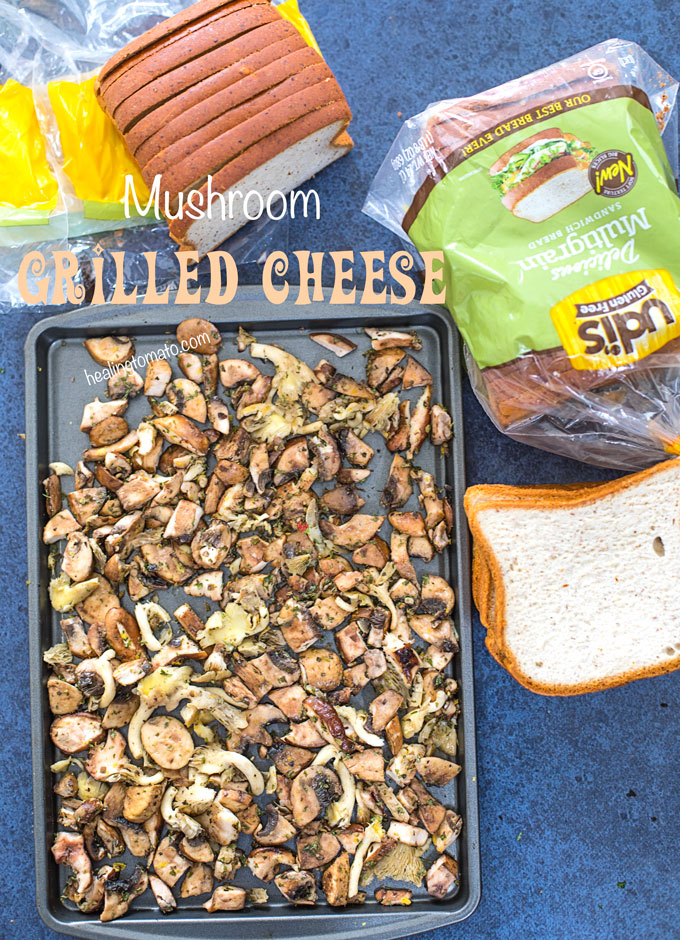 Overhead view of roasted mushroom medley in a baking tray. A Loaf of UDI's Gluten Free Bread with a few slices next to it