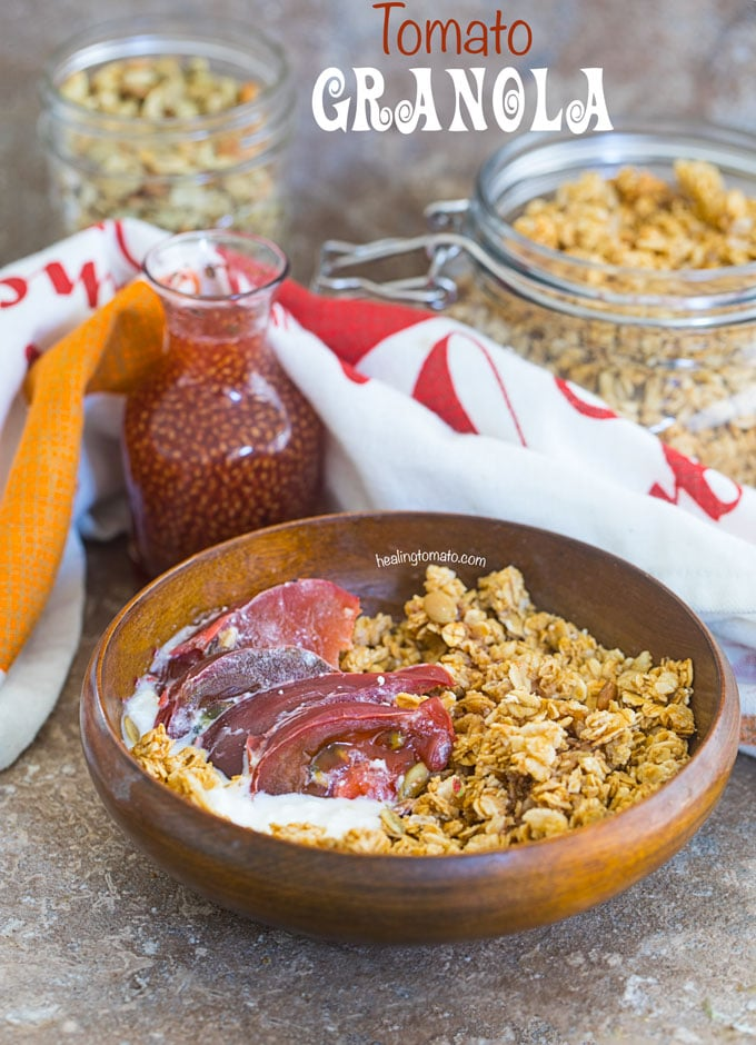 Front view of a brown bowl filled with the tomato granola with the kombucha dressing in the glass bottle. A mason jar with the Granola is in the background
