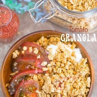 Overhead of a brown bowl filled with the tomato granola with the kombucha dressing in the glass bottle. A mason jar with the Granola is next to it