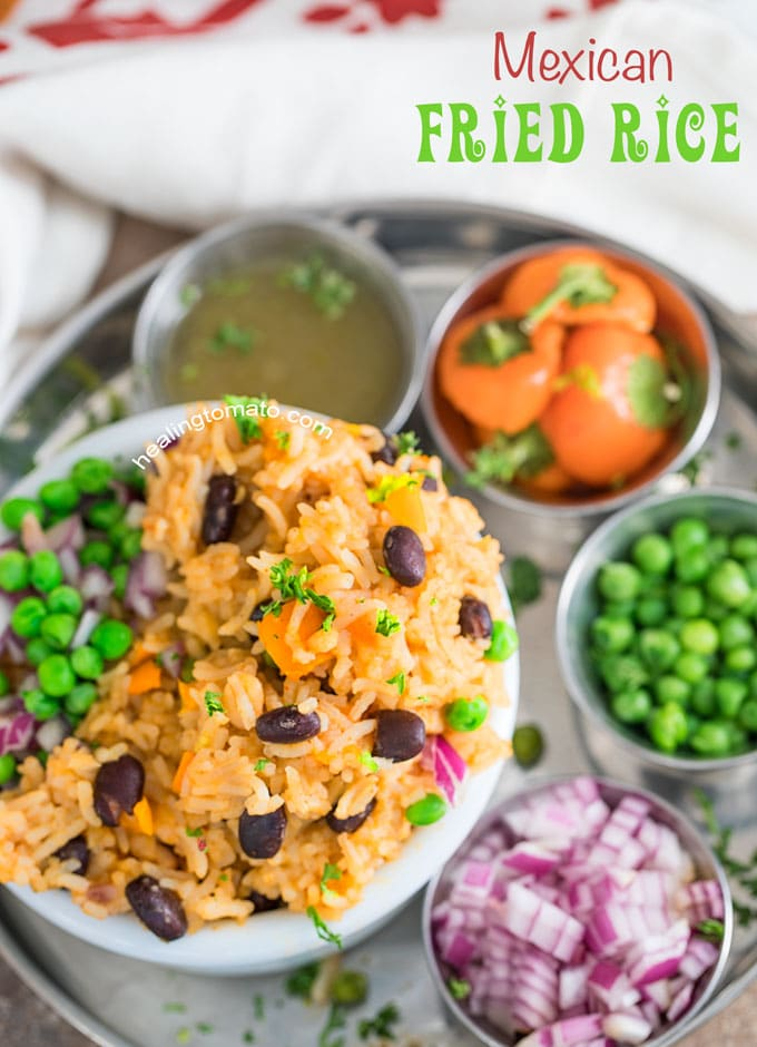 Overhead View of Mexican Fried Rice in a white bowl served with a side of peas, red onion or tomatillos.